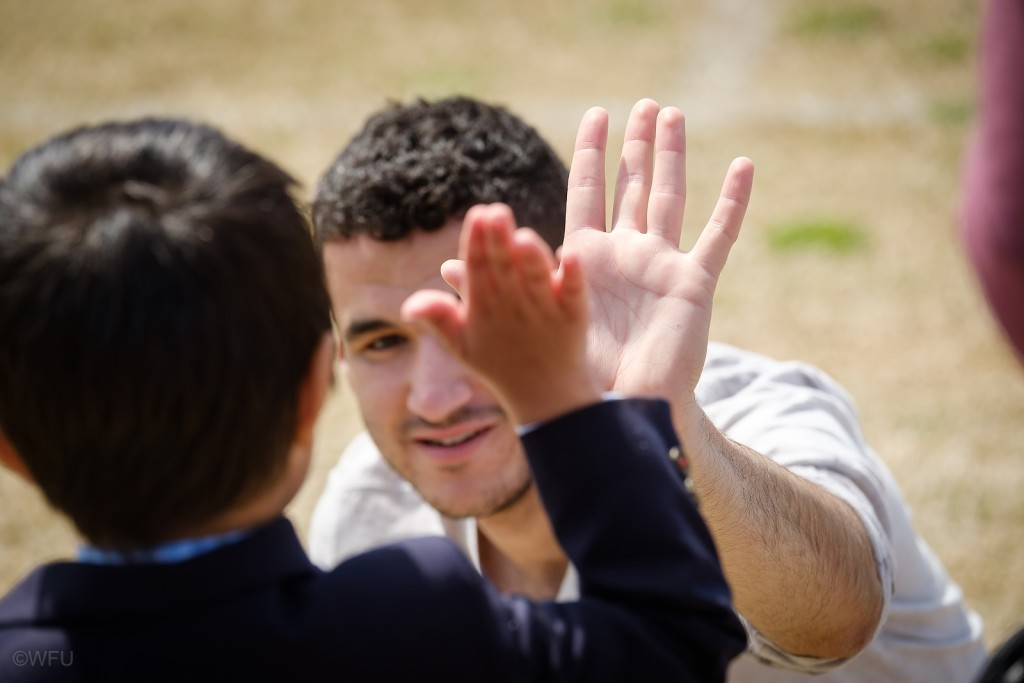 A college student giving a high five to a child at the soccer game